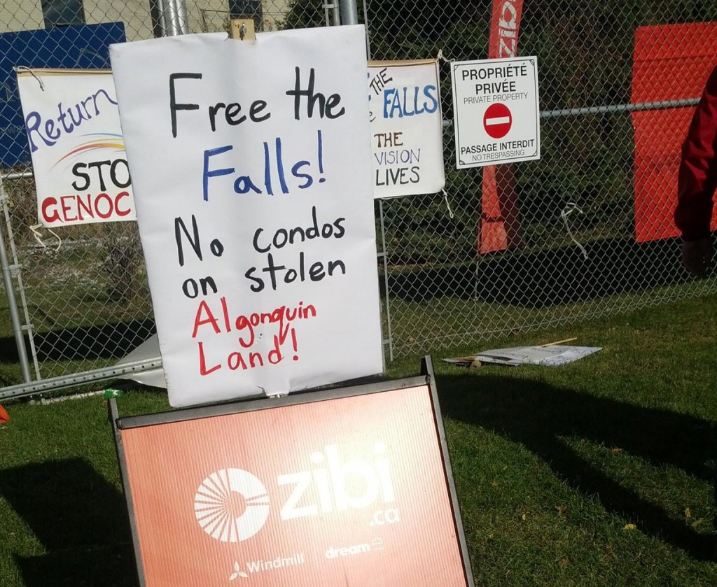 "Photo by Vela Description: A handmade picket sign with the words ""Free the Falls! No condos on stolen Algonquin Land!"" sits directly on top of a corporate orange Zibi logo sign."